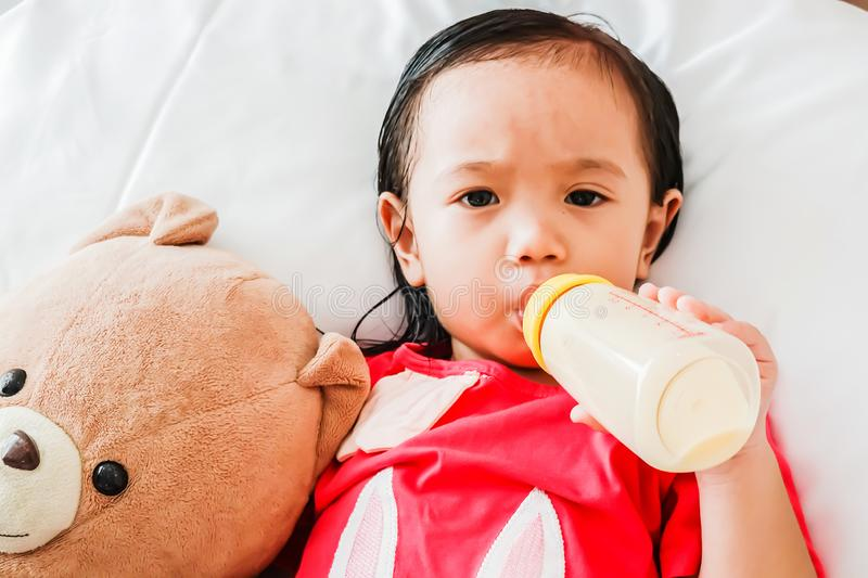 Asian cute baby girl drinking milk from bottle and sleeping on bed stock photos