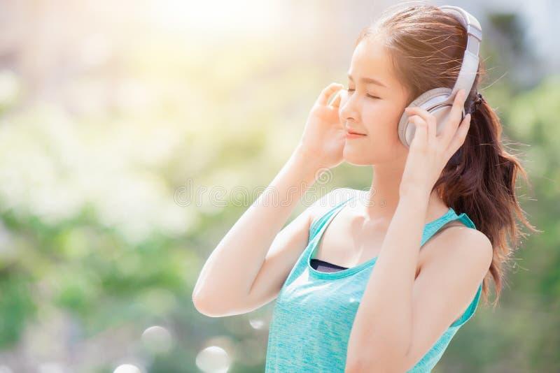 Asian cute beautiful teen listening music with wireless headphone royalty free stock image