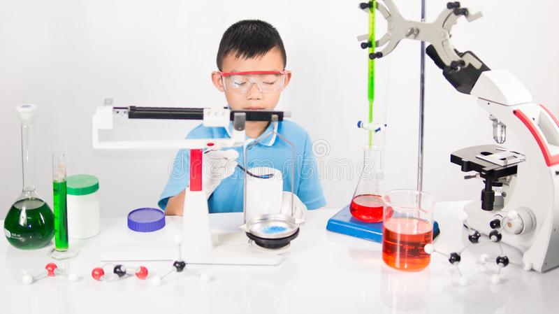 Asian cute child learning science in laboratory on gray whit background. stock photo