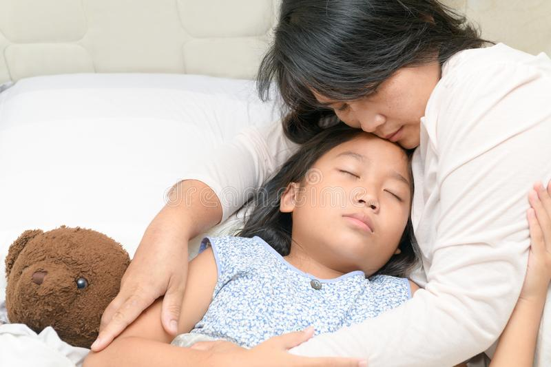 Asian cute daughter hugging mother before sleep royalty free stock photos