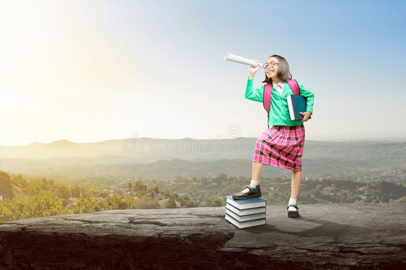 Asian cute girl with a backpack holding the book and paper like a telescope standing and looking at view royalty free stock image