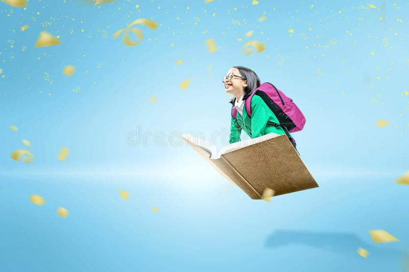 Asian cute girl with glasses and backpack sitting on the book flying. Over blue background royalty free stock photo