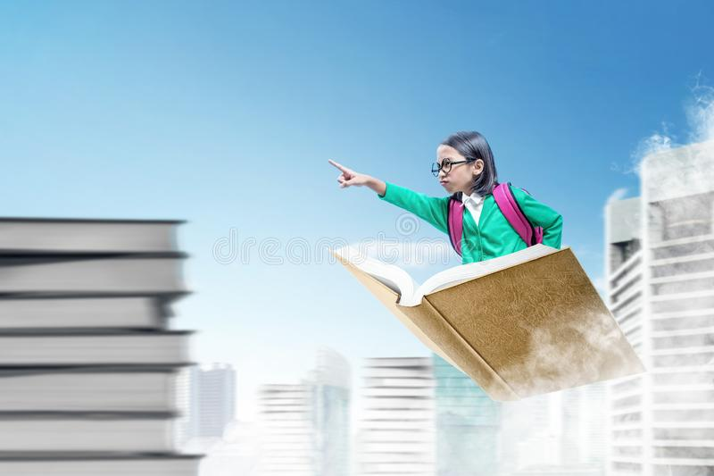Asian cute girl with glasses and backpack sitting on book pointing forward while flying. Above the city stock photography