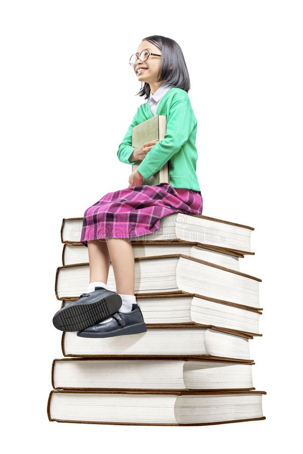 Asian cute girl with glasses holding the book while sitting on the pile of books royalty free stock photo