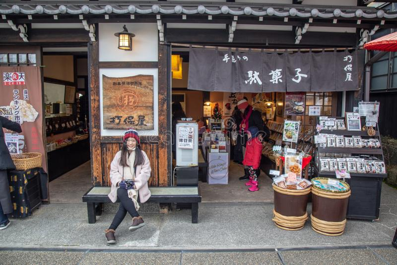 Asian cute girl sit in front of souvenir shop. Hida Takayama, Japan - December 2018 : Asian cute girl sit in front of souvenir shop at Miyagawa Morning Market in stock photography