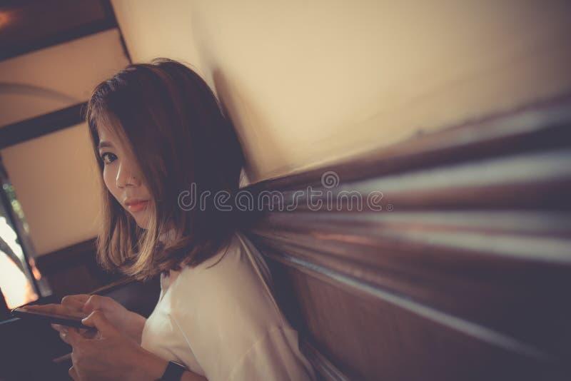 Asian cute girl use smart phone looking at camera royalty free stock image