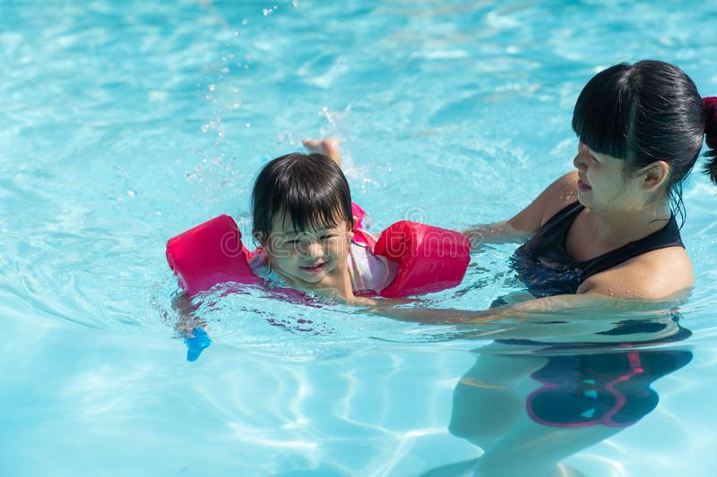 Asian cute little baby girl swimming underwater from mother royalty free stock image