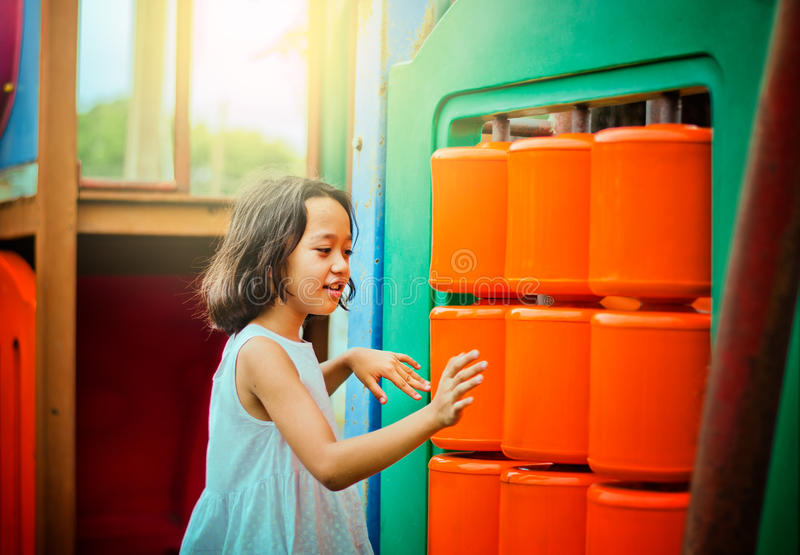 Asian cute little girl playing game in the playground royalty free stock photography