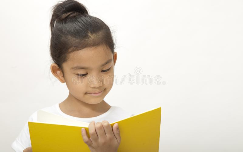 asian cute little reads a book yellow royalty free stock photos