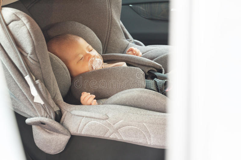 Asian cute newborn baby sleeping in modern car seat. Child new born traveling safety on the road. Safe way to travel fastened seat belts in a vehicle with stock photography
