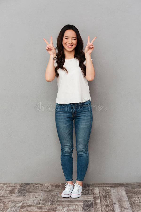 Asian cute woman in casual t-shirt and jeans smiling and gesturing victory sign with both hands, isolated over gray background stock photo
