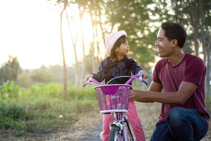 Asian dad help her kid to ride bicycle outdoor royalty free stock photo
