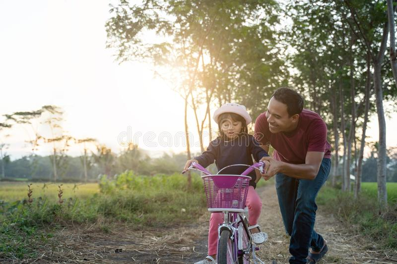 Asian dad help her kid to ride bicycle outdoor stock images