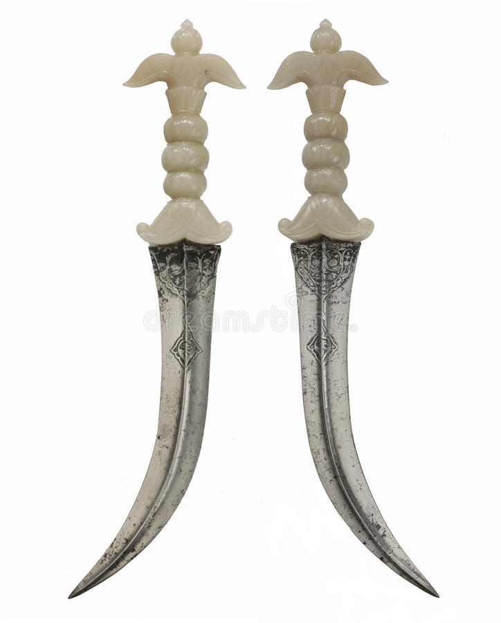 Asian daggers steel curved blade ivory handle crossed for decoration. Rare and unusual Asian daggers with curved steel blade ivory handle gold decorated pins stock photos