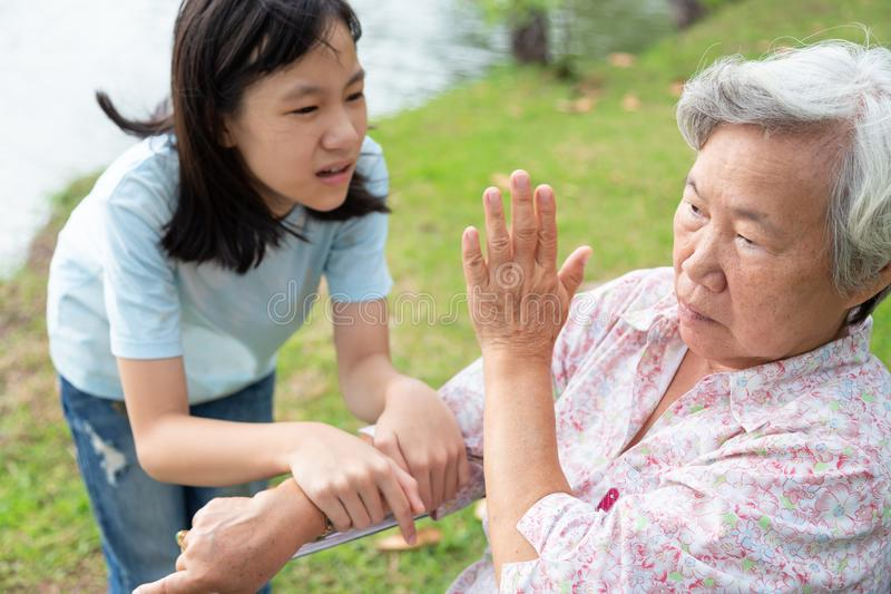 Asian daughter or caregiver hand pouring medicine pills or capsules from bottle,giving pills to senior grandmother in wheelchair royalty free stock photography
