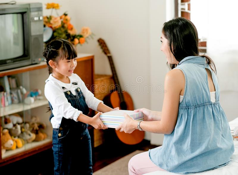 Asian daughter gives gift box to her mother with love in bedroom and some furniture as background stock photos
