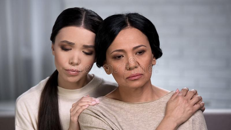 Asian daughter supporting worried mother, problems with health, aging process stock photos