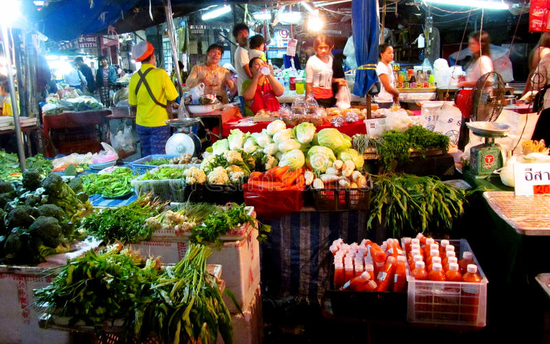 Asian day and night food market in Thailand. Selling fruits, vegetables, nuts, fish, meat, mushrooms and grocery. People selling and buying green and orange stock images
