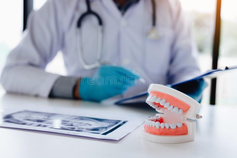 Asian dentist man working in report paper in clinic room.  royalty free stock photos