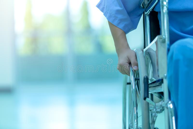 Asian disabled man is sitting in a wheelchair. He holds his hand royalty free stock image