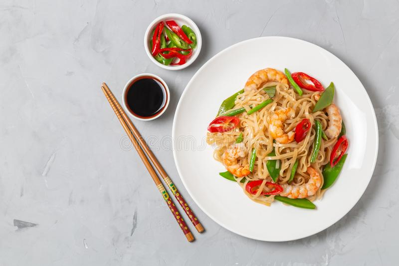 Asian dish of fried rice noodles with shrimp and vegetables. The view from the top. Copy-space. Asian dish of fried rice noodles with shrimp,vegetables and hot royalty free stock photo