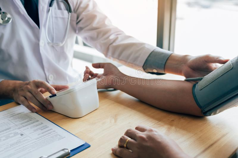 Asian doctor female measuring blood pressure of male patient at clinic office room royalty free stock images