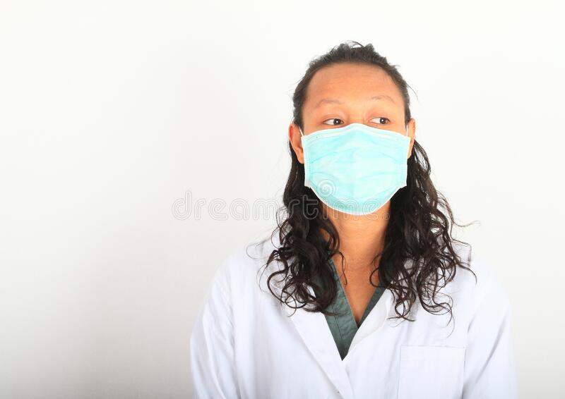 Asian doctor with medical mask. Young woman doctor - pretty Asian girl in white lab coat and medical mask against coronavirus. Virus SARS-CoV-2 and disease COVID royalty free stock image