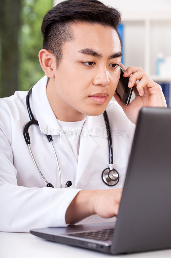 Asian doctor talking on phone stock photo