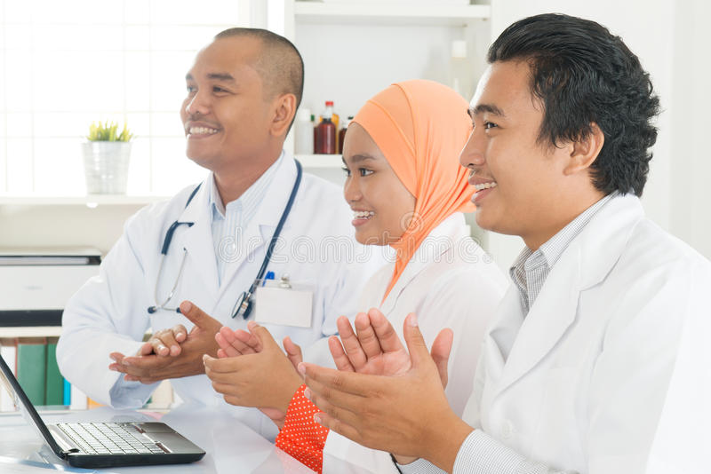 Asian doctors clapping hands royalty free stock photo
