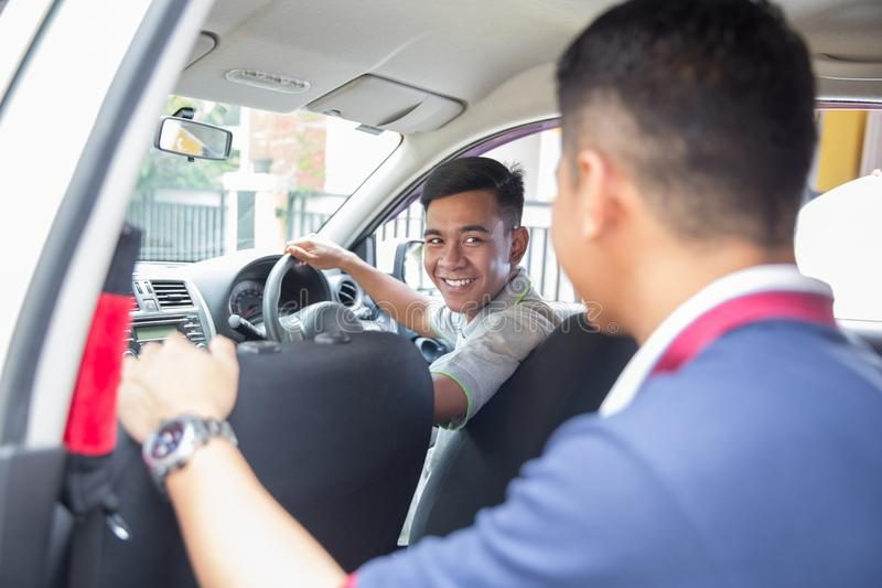 Asian driver smiling to his customer. Young asian driver smiling to his customer sitting on the back of the car stock images