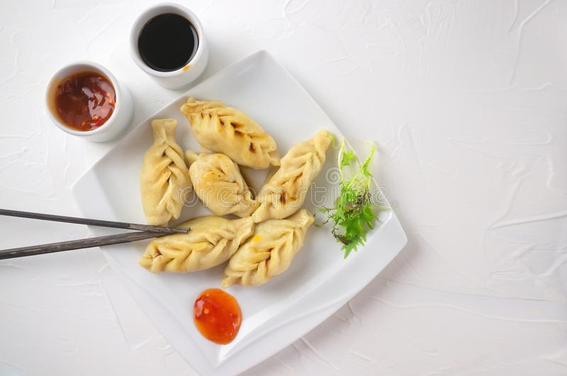 Asian dumplings with chili sauce and soy sauce. Copy space. Selective focus royalty free stock photography