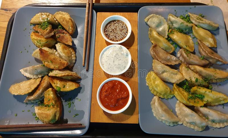 Asian dumplings with spicy dip sauces stock image