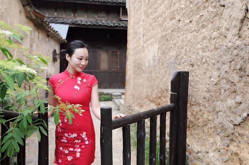 Asian Eastern oriental Chinese woman beauty in traditional ancient dress costume red cheongsam in ancient town garden fence stock image