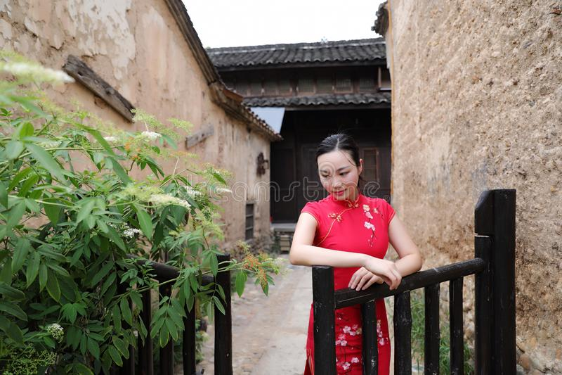 Asian Eastern oriental Chinese woman beauty in traditional ancient dress costume red cheongsam in ancient town garden fence stock photos