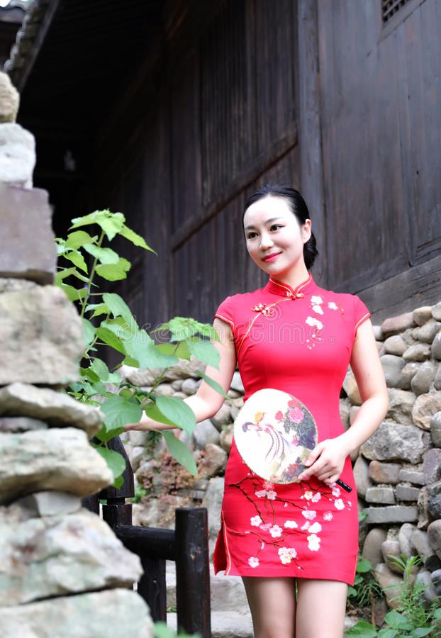 Asian Eastern oriental Chinese woman beauty in traditional ancient dress costume red cheongsam in ancient town old culture fashion stock photo