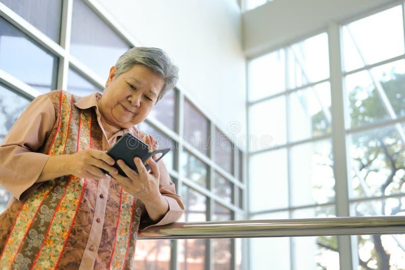 Asian elder woman holding mobile phone on terrace. elderly senior using smartphone on patio. Asian elder woman holding mobile phone on terrace. elderly female stock photo