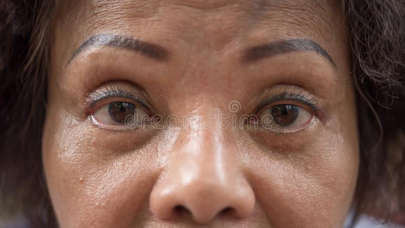 Asian elder women show her eyes and eyebrow tattoo. Asian elder woman 60s with black hair and wrinkled on face show her eyes and eyebrow tattoo before cornea stock images