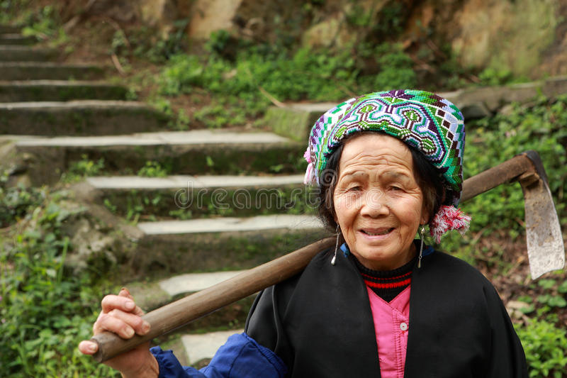 Asian elderly Chinese woman farmer peasant with hoe on shoulder. Pingan Village, Guangxi Province, China - April 5, 2010: Elderly farmer peasant woman coming royalty free stock images