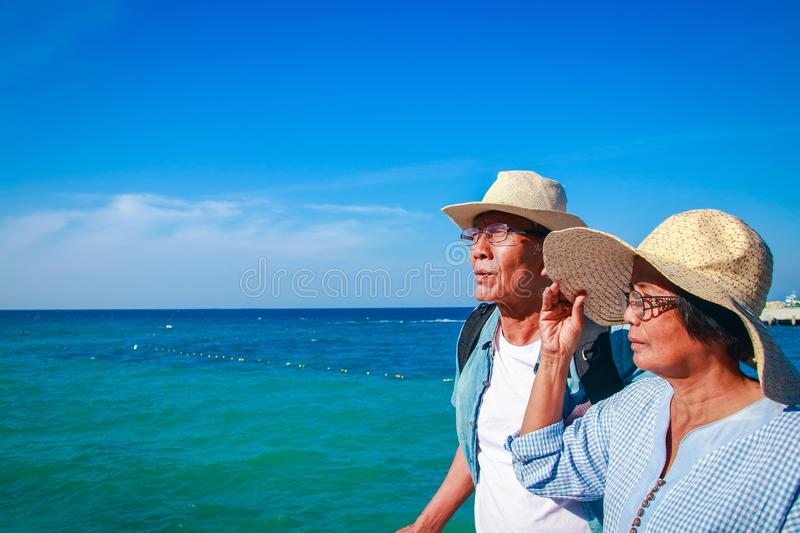 Elderly Asian couple visiting the sea. Asian elderly couple Travel after retirement Went to the sea very happy royalty free stock photo