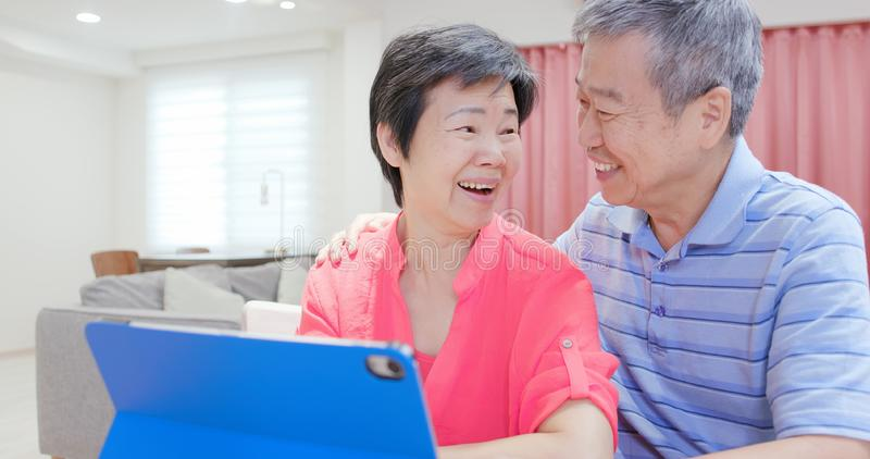Elderly couple use digital tablet. Asian elderly couple use digital tablet happily at home royalty free stock photo