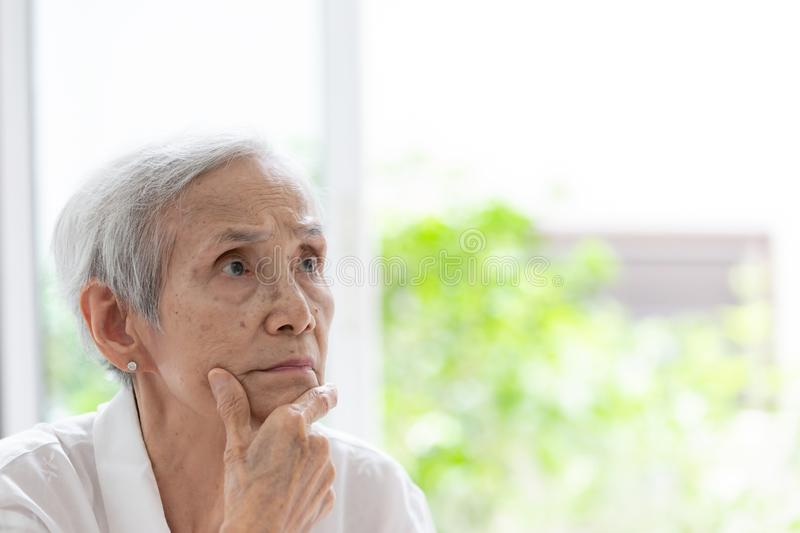 Asian elderly people with crossed arms and hand raised on chin,think positive,analytical thinking searching,closeup portrait of royalty free stock images