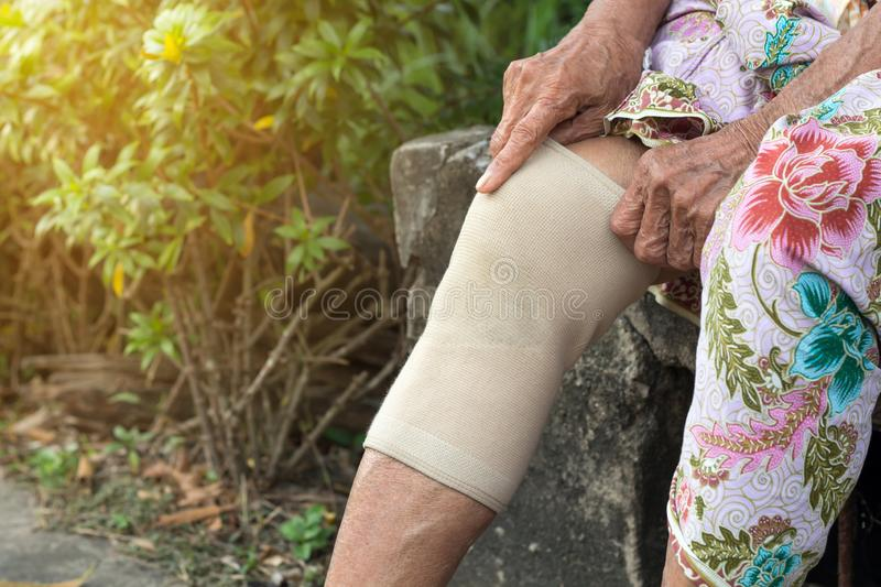 Asian Elderly people or older woman wearing the knee support or athlete knee strap to decrease knee pain,healthy concept stock images