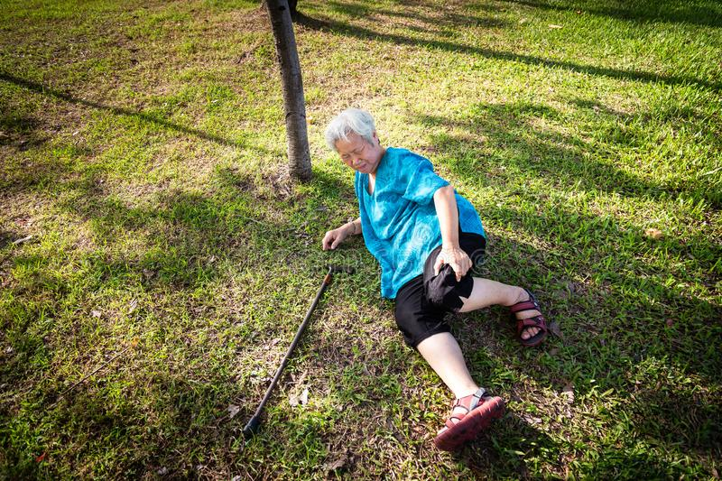 Asian elderly people with walking stick on floor after falling down in summer outdoor park,sick senior woman fell to the floor stock photos