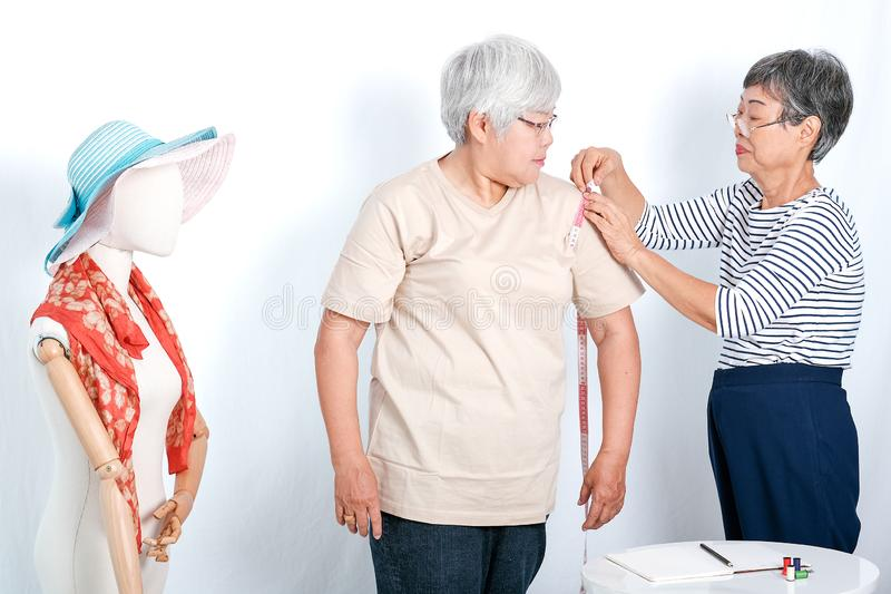 Asian elderly tailor woman show action of body measurement for the other elderly customer near cloth puppet. Image is isolated on. Asian elderly tailor women royalty free stock image