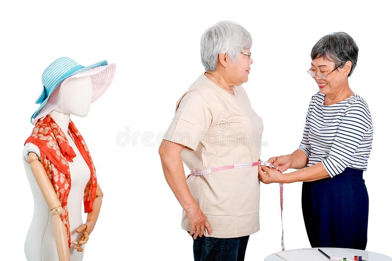 Asian elderly tailor woman show action of body measurement for the other elderly customer near cloth puppet. Image is isolated on. Asian elderly tailor women stock image