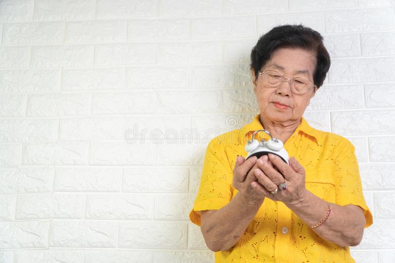 Asian elderly woman holding a white alarm clock, here face shows anxiety. The concept aging society That needs time and grandchild. Ren to come back to caring stock image