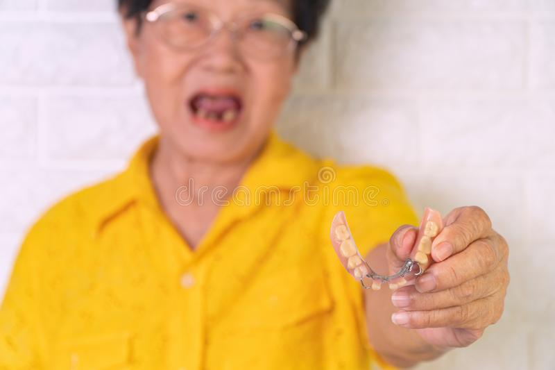 Asian Elderly woman over 70 years old be smile with a few broken teeth and holding dentures in hand. Dentures for prosthetic devic royalty free stock images
