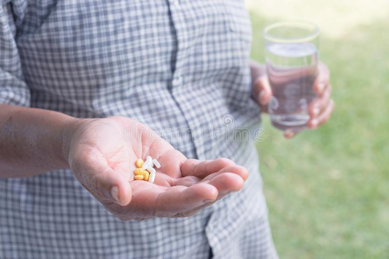 Asian elderly woman are taking and eating medicines and vitamins royalty free stock photo