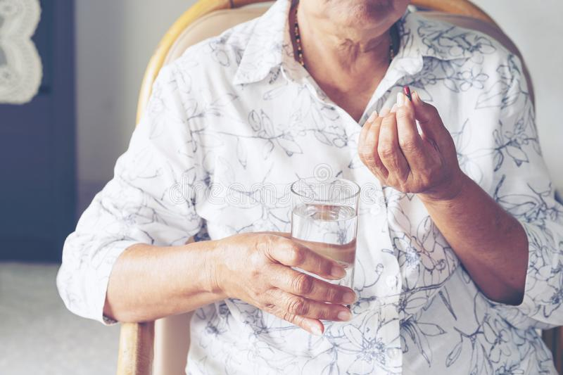 Asian elderly woman are taking and eating medicines and vitamins stock photos