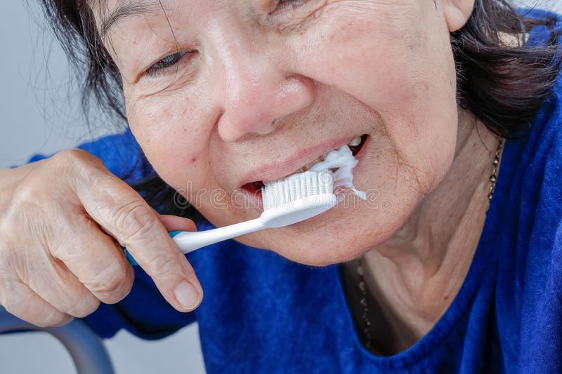 Asian elderly woman trying use toothbrush ,hand tremor. royalty free stock image